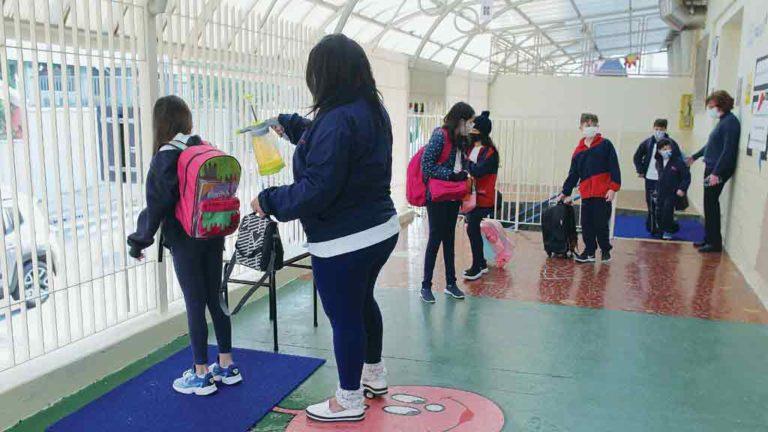 DESINFECÇÃO Aluna tem a mochila borrifada com álcool ao chegar à escola
